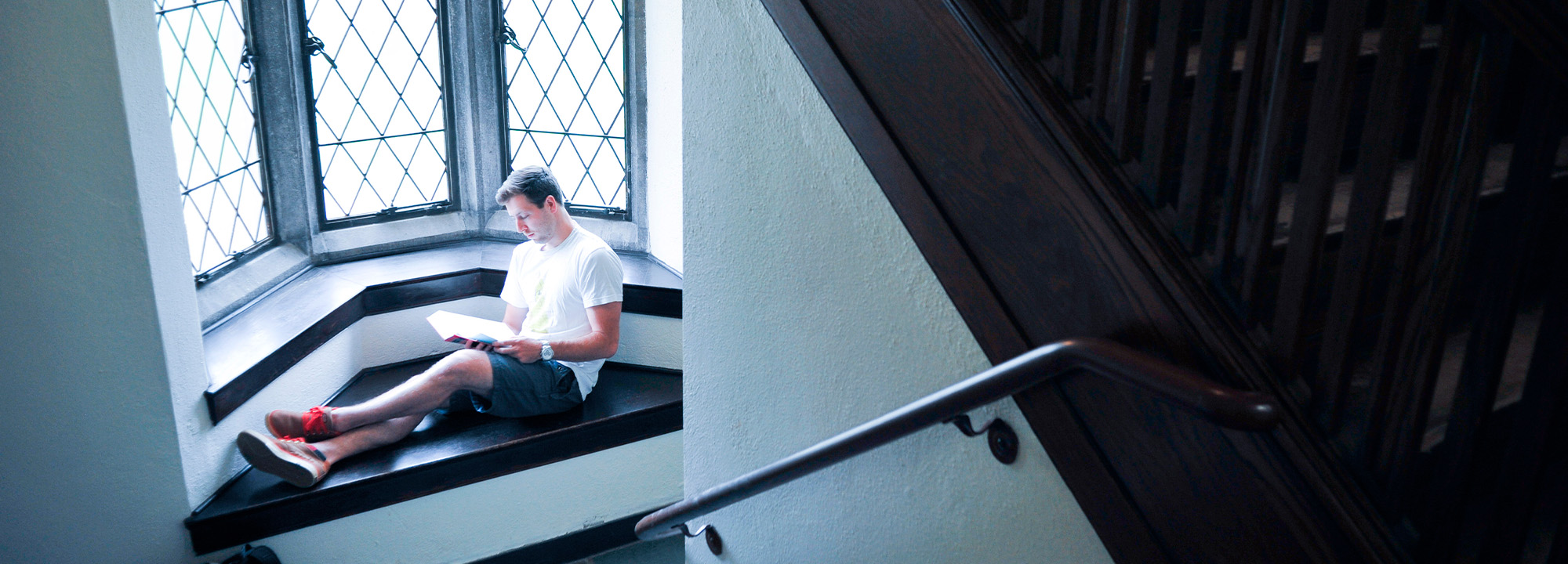 Student reading in a stairwell