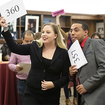 Law student Abby Marchinkoski and friend Tavis Fitzpatrick during bidding at the annual PILG Auction, which supports public interest fellowships.